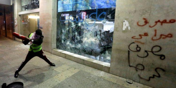 Un manifestante intenta romper un escaparate de un banco en Beirut, la capital libanesa, la noche del 14 de enero de 2020 (AFP).