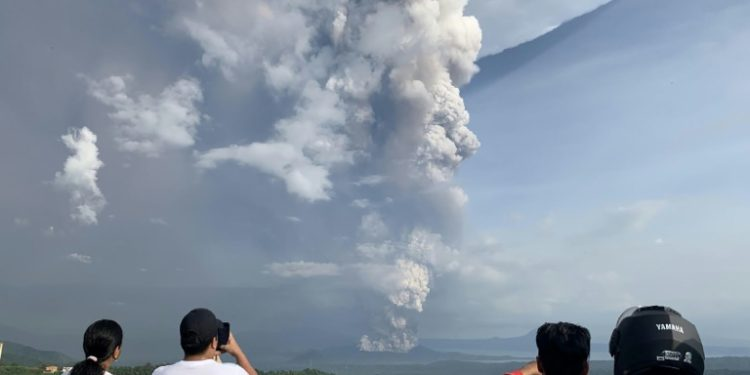 Personas tomando fotos de la nube de cenizas lanzada por el volcán Taal, uno de los más activos de Filipinas, el 12 de enero de 2020.