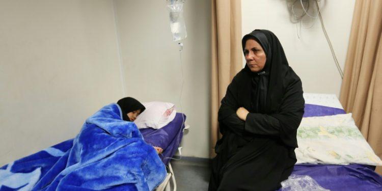 Una iraní, sentada junto a una allegada herida en la estampida registrada durante el funeral del comandante de los Guardianes de la Revolución Qasem Soleimani, el 7 de enero de 2010 en el hospital Bahonar de Kermán (AFP).