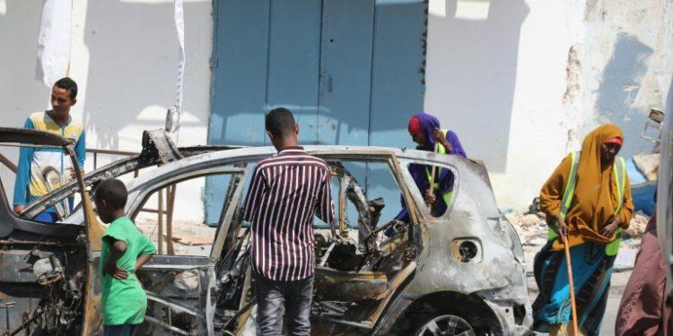 Varias personas limpian el escenario de un atentado con coche bomba en Mogadiscio el 8 de enero de 2020 (AFP).