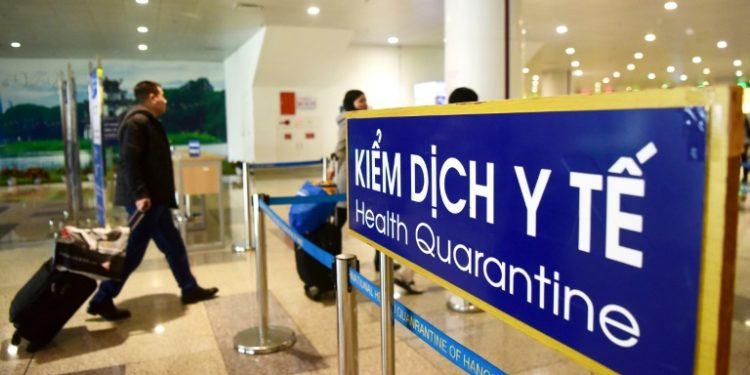 Unos pasajeros pasan junto a un cartel de cuarentena sanitaria tras aterrizar en el aeropuerto internacional de Noi Bai, en Hanói, el 21 de enero de 2020 (AFP).