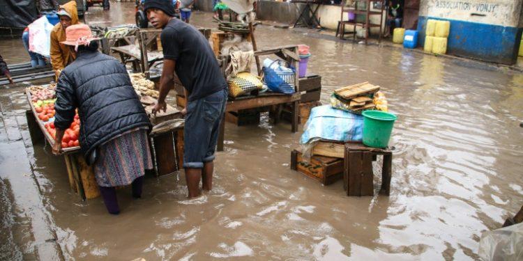 Comerciantes intentan salvar sus bienes en un mercado de Antananarivo, anegado por las lluvias del 8 de enero de 2020. (AFP).