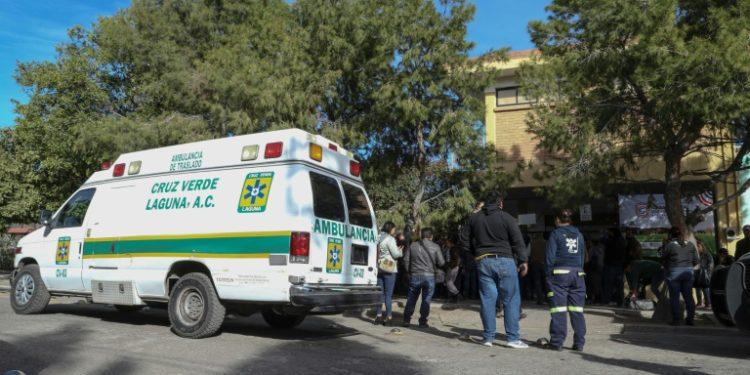 Paramédicos y familiares se reúnen fuera de la escuela primaria, donde un niño de 11 años disparó y mató a su maestra e hirió a seis personas antes de suicidarse en Torreón, México, el 10 de enero de 2020 (AFP)