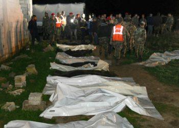 Una imagen divulgada el 17 de febrero de 2020 por la agencia oficial siria SANA muestra fuerzas gubernamentales trabajando en la extracción de cadáveres de la fosa común hallada en la región de Guta oriental, unos 20 km al este de Damasco. (AFP).