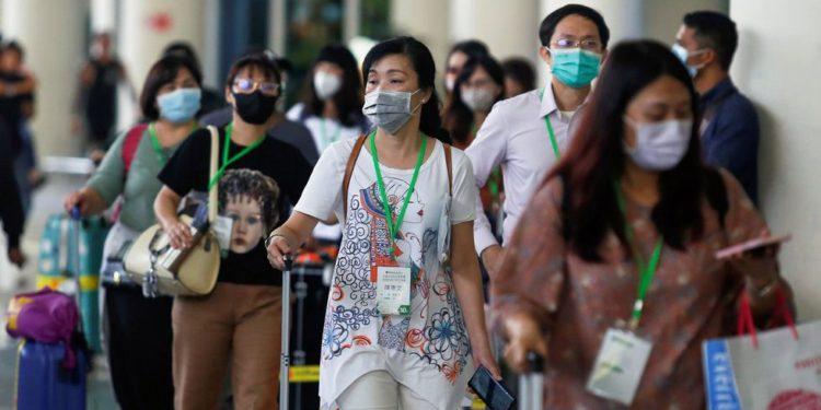 Pasajeros usan mascarillas en Bali, Indonesia. Chile también ha anunciado que reforzó los controles en sus aeropuertos. (REUTERS).