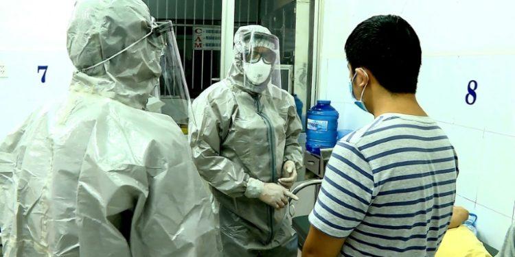 Personal médico con trajes de protección habla con pacientes en una habitación de aislamiento en un hospital en Ho Chi Minh, Vietnam. (AFP).