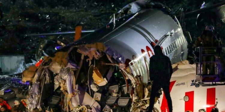 Un hombre contempla la parte central del avión de la compañía Pegasus Airlines que se partió en tres pedazos tras salirse de la pista en el aeropuerto Sabiha Gokcen, el 5 de febrero de 2020 en Estambul. (AFP).