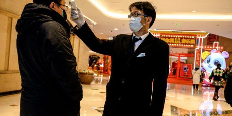 Un guardia de seguridad comprueba la temperatura de un hombre en un centro comercial en Shangái (China), el 8 de febrero de 2020. (AFP).